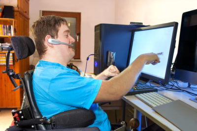 Man in wheelchair and talking on headset points at computer screen.
