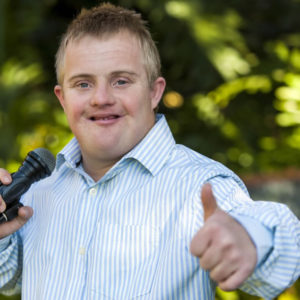 Man with microphone giving thumbs up.