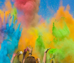 Many hands throwing dried colors into the air for a Holi Festival.