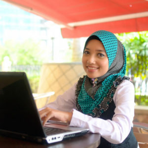Woman sitting at a laptop and smiling .