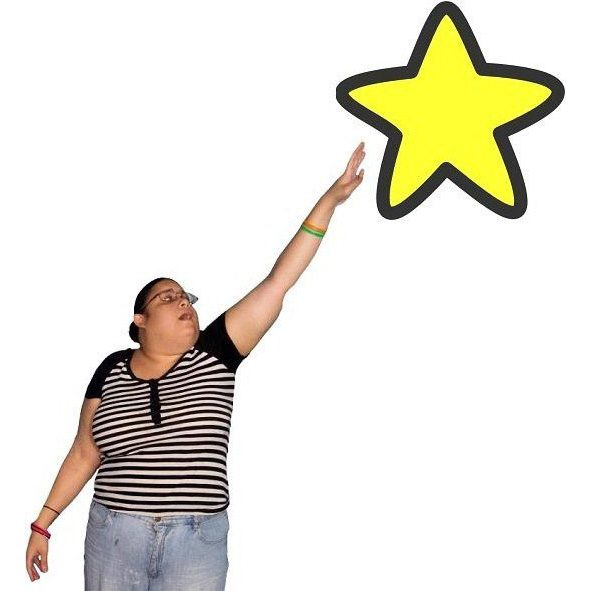 A woman reaching for a star above her.
