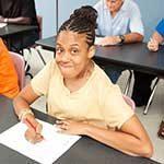 Woman writing at a desk and smiling at the camera.